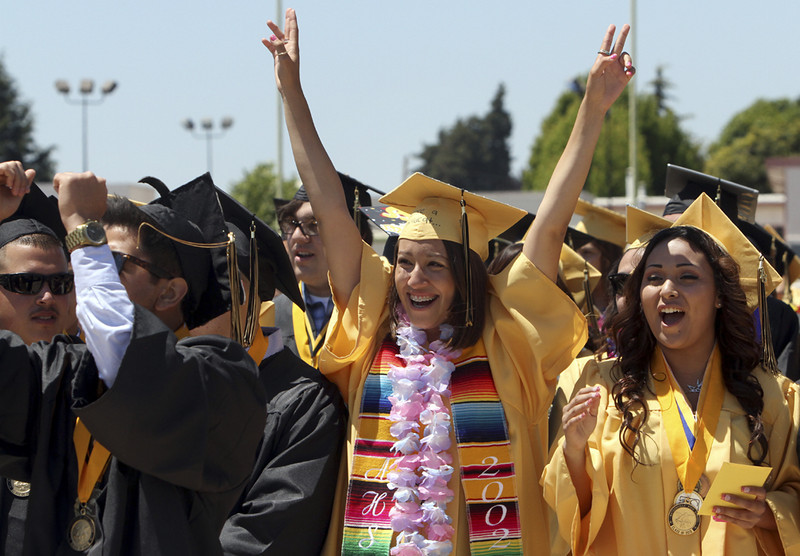 . Watsonville High graduates jump from their seats and cheer on their classmates during the 2013 graduation ceremony on Friday. (Kevin Johnson/Sentinel)