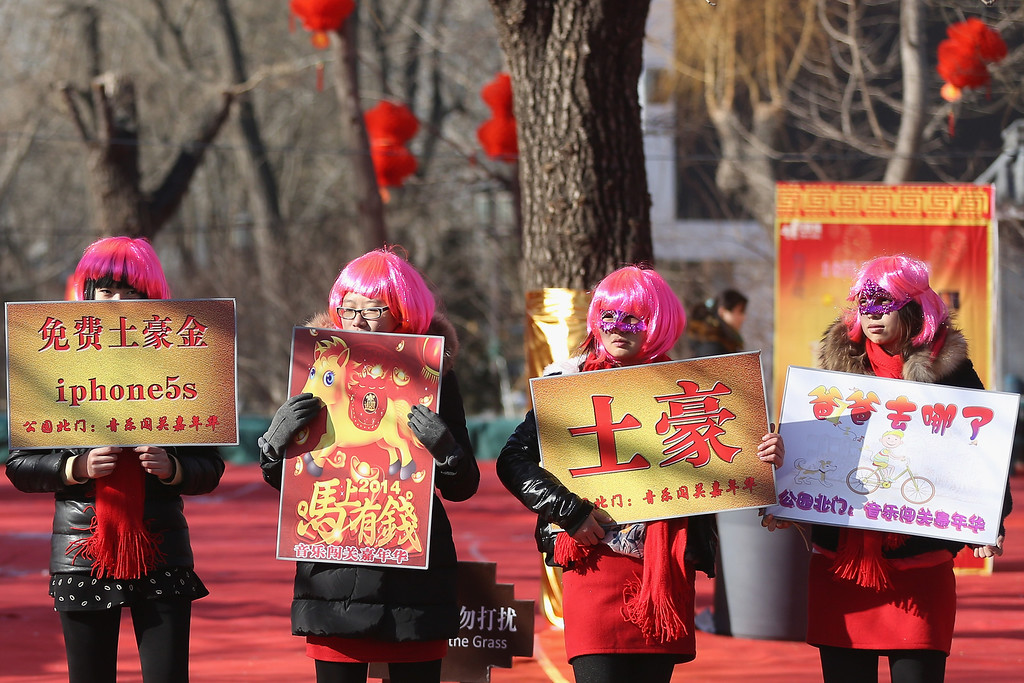 . Chinese young women show brand to guide visitors at the Spring Festival Temple Fair for celebrating Chinese Lunar New Year of Horse at the Temple of Earth park on January 30, 2014 in Beijing, China.   (Photo by Feng Li/Getty Images)