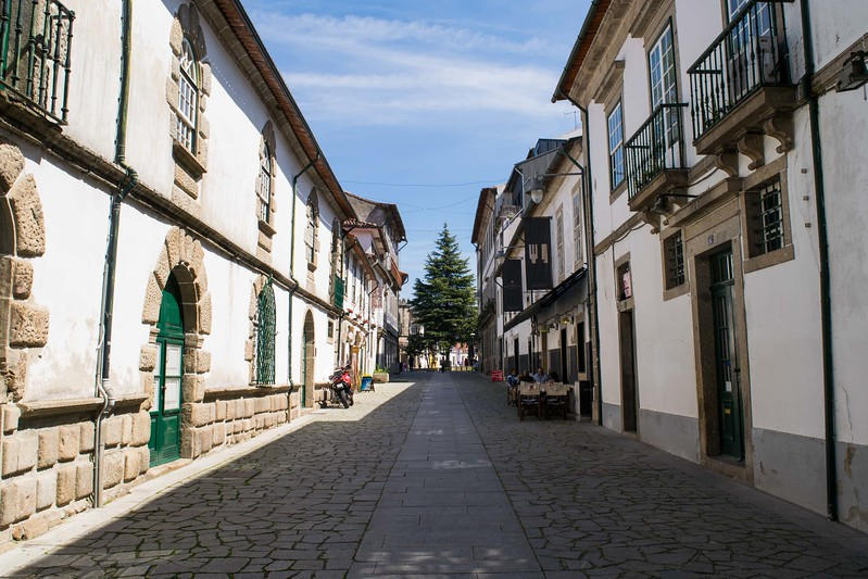 Street lined with white buildings and beige brick arches in Braga.