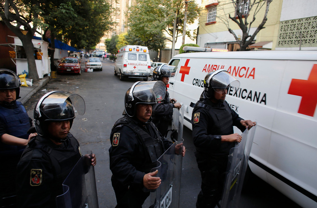 . Ambulances pass a police line near the headquarters of state oil giant Pemex in Mexico City January 31, 2013. An explosion rocked Pemex on Thursday, killing at least 14 people and injuring 80 others, the government said. The blast, which media reports said was caused by machinery, hit the lower floors of the downtown building, throwing debris into the streets and sending workers running outside.  REUTERS/Tomas Bravo