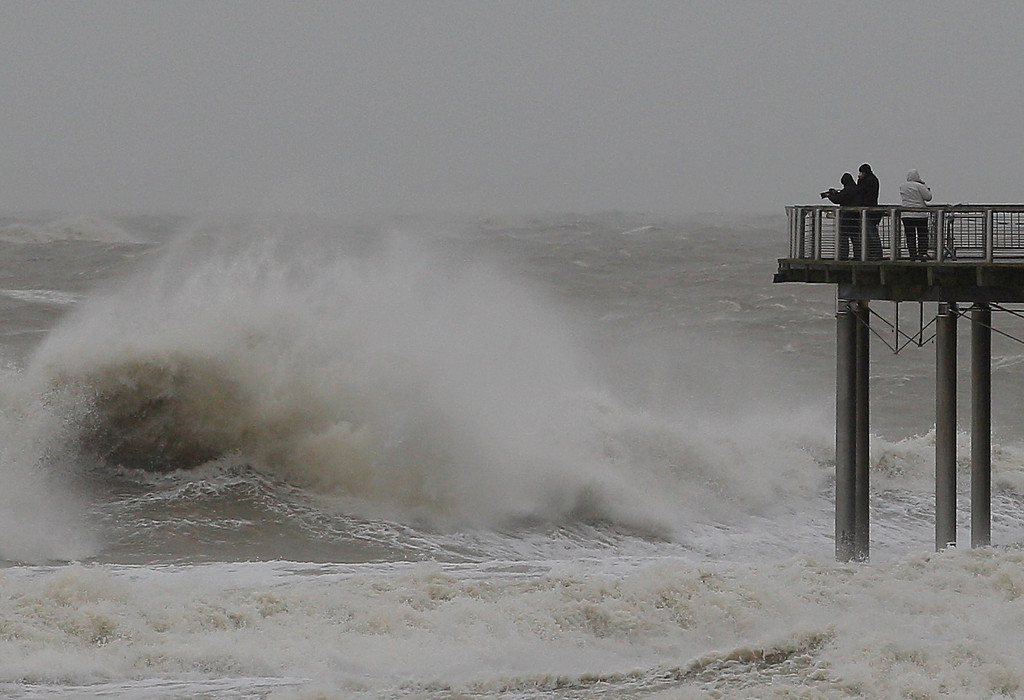 . Spectators look at the strong North Sea waves at a coastal town in Blankenberge, Belgium, Thursday, Dec. 5, 2013. A severe storm will hit the Belgian coast at full force overnight. (AP Photo/Yves Logghe)