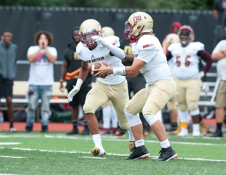 09/21/18  Wesley Bunnell | Staff  New Britain football at South Windsor High School on Friday afternoon. QB Tahje Yopp (4) hands off to RB Kaiyon Gunn (1).