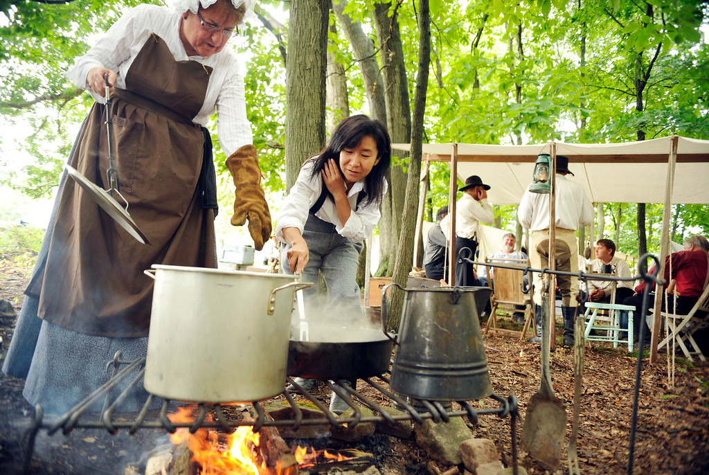 ". Satomi Okada, 52, pulls her hair back as she transfers chicken thighs from a cast iron skillet to a soup pot under the guidance of re-enactor Candy Girard, 62 of Omaha, Neb., at the Blue Gray Alliance\'s re-enactment camp outside Gettysburg, Pa., on Friday, June 28, 2013. Okada, who is from Kobe, Japan, has a three-month tourist visa and is trying to learn what she can about the Civil War, which in Japan is called ""the North-South War.\"" A Minnesota friend of hers is re-enacting, and brought her along for the ride. Okada will be a \""powder monkey\"" -- assisting with the cannons -- with Terry\'s Texas Rangers Company H during the re-enactments. Some women did go to war -- in cognito -- with their brothers, fathers or husbands during the Civil War, and more than a few female re-enactors today are portraying that by abandoning the hoop skirts and petticoats in favor of men\'s wear and artillery. DAILY RECORD/SUNDAY NEWS - CHRIS DUNN"