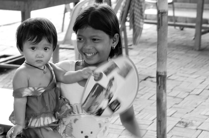 Sisters outside the temple enjoying a Smiling Albino fan