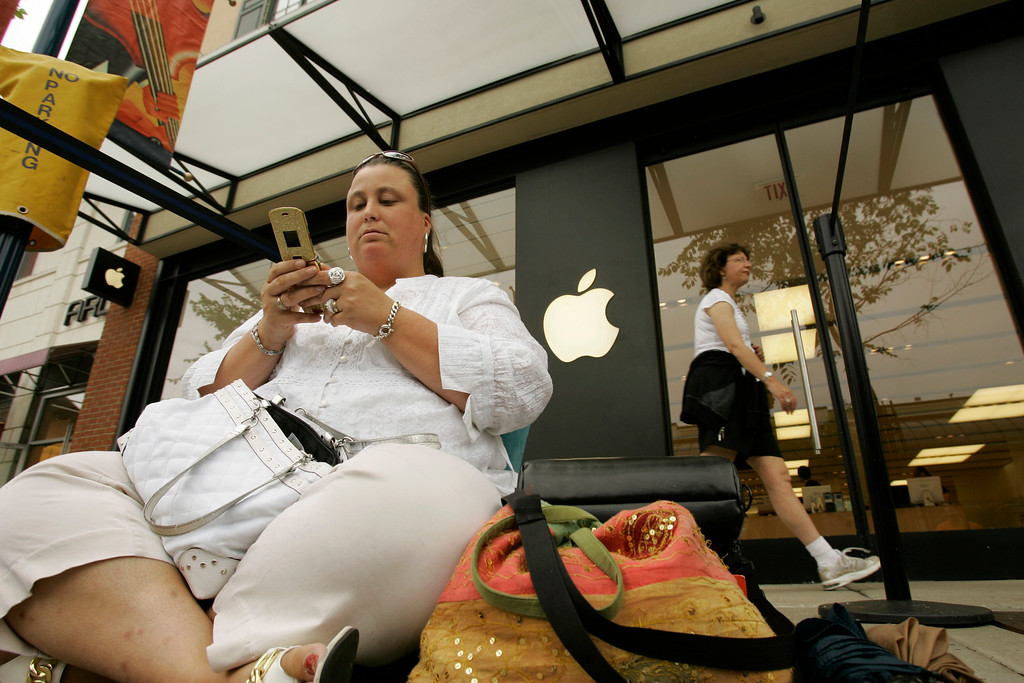 . Michelle Schleppi text-messages her friend in front of an Apple store while waiting for the iPhone, Friday, June 29, 2007 in Columbus, Ohio. Schleppi said she had scoped out the Columbus Apple location since midnight Friday but saw no one else around, so she didn\'t try waiting until 6 a.m. Security at the outdoor shopping center chased her away and didn\'t allow the line to start forming until two hours later, she said. Schleppi was the first one in line at the store. (AP Photo/Kiichiro Sato)