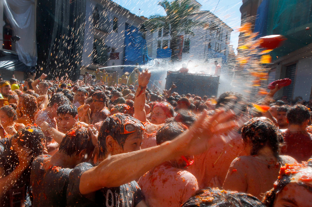 ". Crowds of people throw tomatoes at each other during the annual ""tomatina\"" tomato fight fiesta in the village of Bunol, 50 kilometers outside Valencia, Spain, Wednesday, Aug. 27, 2014.  Some thousands of people are splattering each other with tons of tomatoes in the annual \""Tomatina\"" battle. Bunol town says some 20,000 people are taking part in Wednesday\'s hour-long street bash, inspired by a food fight among kids back in 1945.  (AP Photo/Alberto Saiz)"