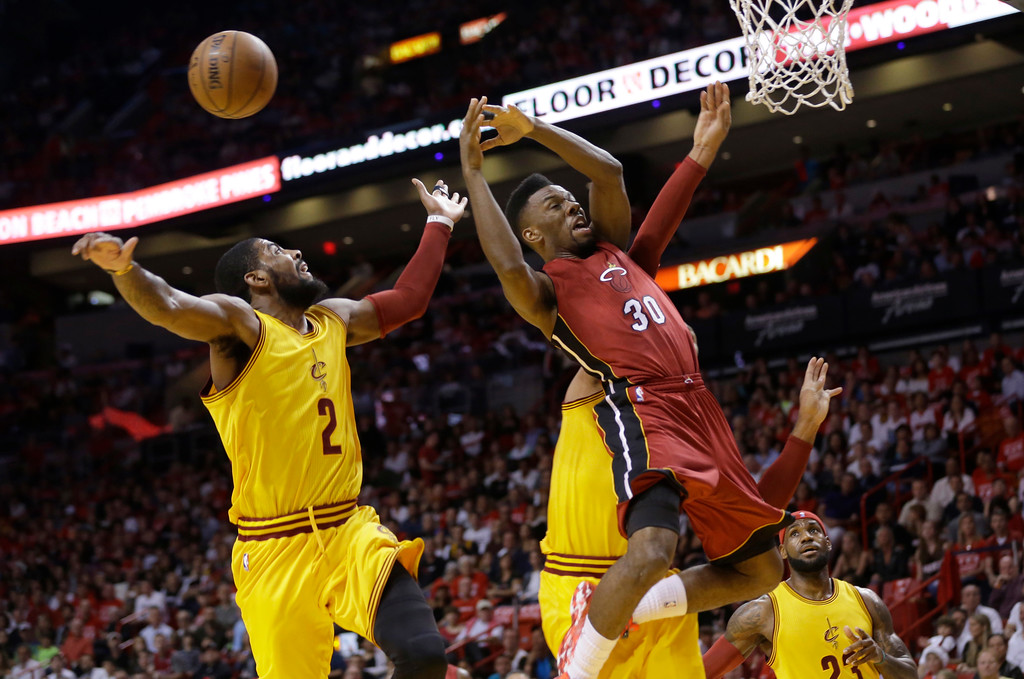 . Miami Heat guard Norris Cole (30) loses control of the ball after being fouled by Cleveland Cavaliers\' Shawn Marion (partially obscured) during the first half of an NBA basketball game, Thursday, Dec. 25, 2014, in Miami. Cavaliers guard Kyrie Irving (2) and forward LeBron James (23) look on. (AP Photo/Lynne Sladky)