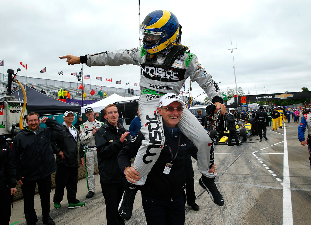 . Sebastien Bourdais celebrates on the shoulders of his father, Patrick, after winning the second race of the IndyCar Detroit Grand Prix auto racing doubleheader in Detroit on Sunday, May 31, 2015.  (AP Photo/Paul Sancya)