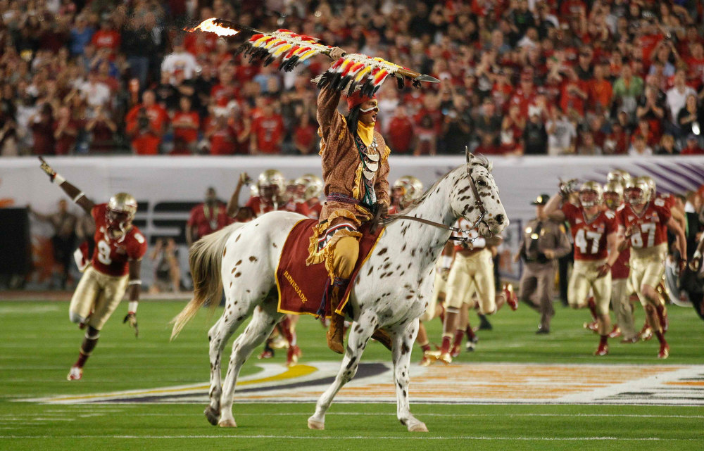 Description of . Mascots Osceola, riding Renegade, lead the Florida State Seminoles onto the field to play against the Northern Illinois Huskies during the 2013 Discover Orange Bowl NCAA football game in Miami, Florida January 1, 2013.  REUTERS/Jeff Haynes