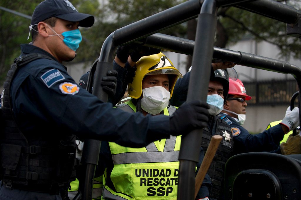 . Rescuers are driven inside the premises of the skyscraper that houses the headquarters of state-owned Mexican oil giant Pemex, following a blast inside the building in Mexico City on January 31, 2013.   YURI CORTEZ/AFP/Getty Images