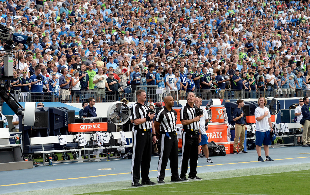 . Officials stand on the sideline of the Seattle Seahawks during the playing of the national anthem before an NFL football game between the Seahawks and the Tennessee Titans Sunday, Sept. 24, 2017, in Nashville, Tenn. Neither team came out onto the field for the anthem. (AP Photo/Mark Zaleski)