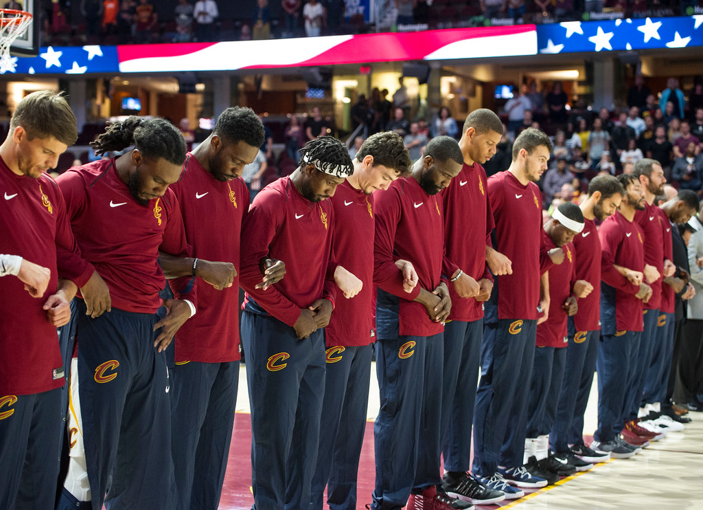 . Members of the Cleveland Cavaliers lock arms as they listen as the national anthem is played before an NBA pre-season basketball game against the Atlanta Hawks in Cleveland, Wednesday, Oct. 4, 2017. (AP Photo/Phil Long)