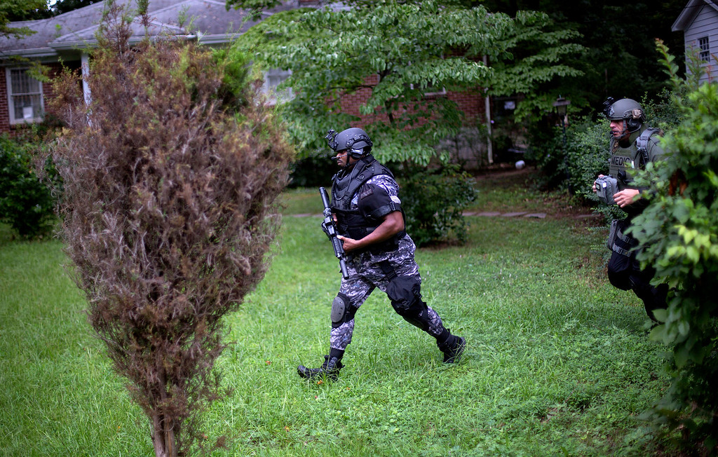 . Dekalb County Police SWAT officers run though the front yard of a home toward Ronald E. McNair Discovery Learning Academy after reports of a gunman entered the school, Tuesday, Aug. 20, 2013, in Decatur, Ga.  Superintendent Michael Thurmond says all students at Ronald E. McNair Discovery Learning Academy in Decatur east of Atlanta are accounted for and safe Tuesday and that he is not aware of any injuries. (AP Photo/David Goldman)