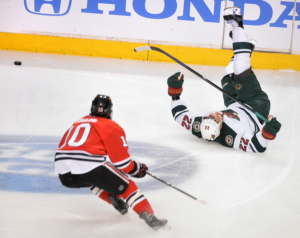 . Minnesota\'s Nino Niederreiter, right, is upended while pursuing the puck with Chicago\'s Patrick Sharp during the first period. (Pioneer Press: Ben Garvin)