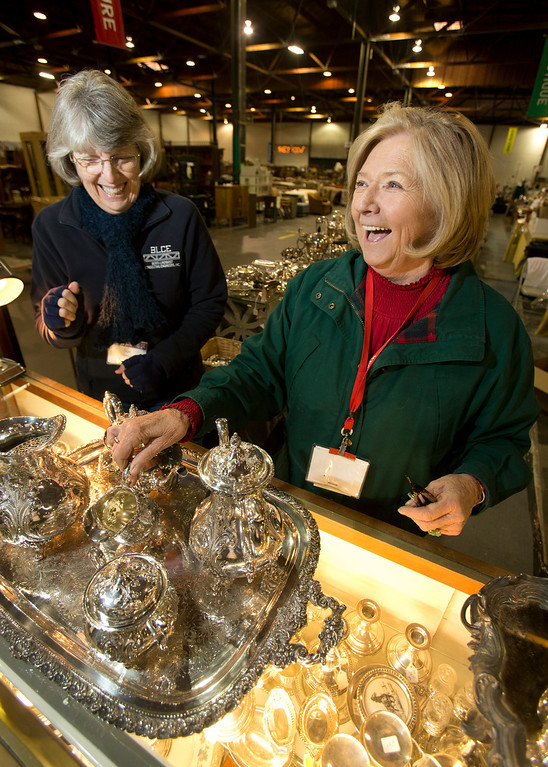. Sue Lindquist, left, sale co-chair, and Sheri Guthrie, president of the Oakland Museum Women\'s Board, peruse a Sterling silver tea set as they prepare for the annual White Elephant Sale, inside the organization\'s 96,000-square-foot warehouse in Oakland, Calif., Tuesday, Jan. 15, 2013. (D. Ross Cameron/Staff)