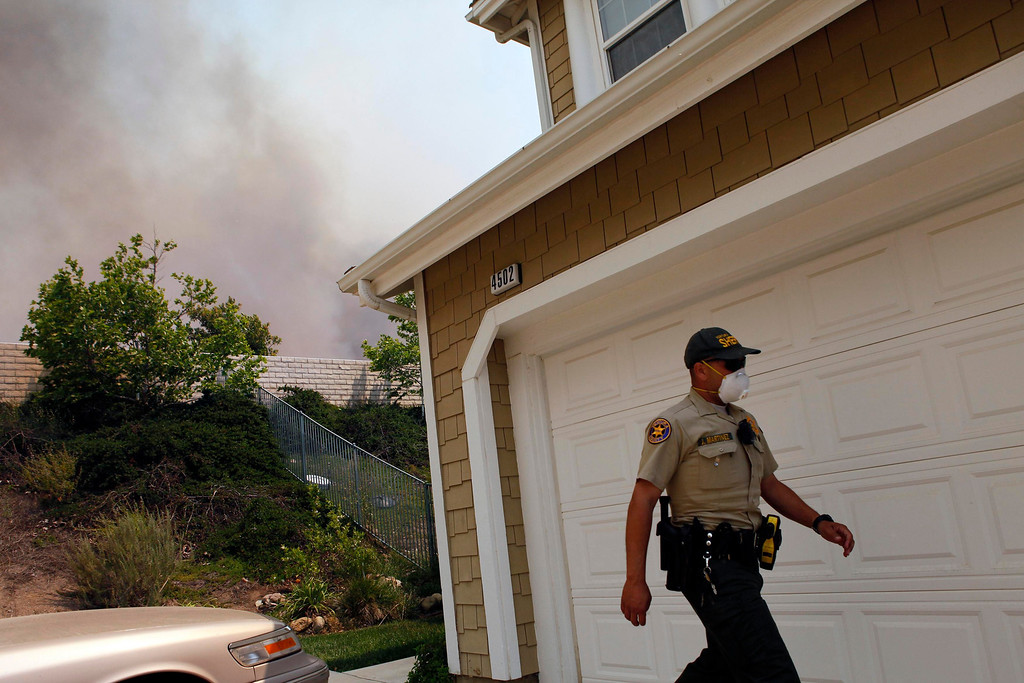 . A police officer walks to evacuate residents from a fast moving brush fire in the Newbury Park area of Ventura County May 2, 2013.  REUTER/Patrick T. Fallon