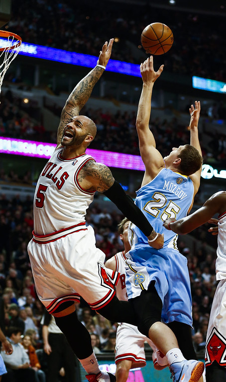 . Denver Nuggets center Timofey Mozgov of Russia (R) grabs a rebound behind Chicago Bulls forward Carlos Boozer (L) in the first half of their NBA game at the United Center in Chicago, Illinois, USA, 21 February 2014  EPA/TANNEN MAURY