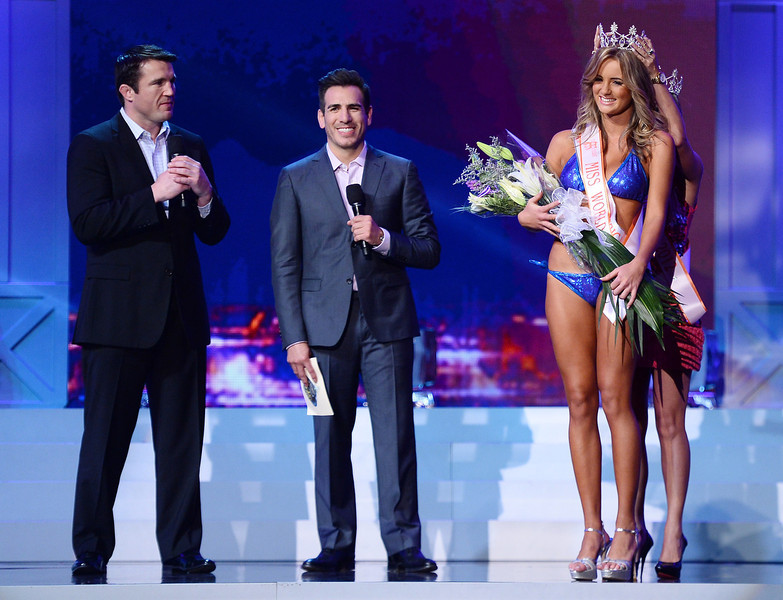 . Co-host and mixed martial artist Chael Sonnen, and co-host and former mixed martial artist Kenny Florian look on as Miss Hooters World 2012 Evelise Giorge de Souza of Brazil crowns Kirsten Martins (front) of South Africa Miss Hooters World 2013 during the 17th annual Hooters International Swimsuit Pageant at The Joint inside the Hard Rock Hotel & Casino on June 27, 2013 in Las Vegas, Nevada.  (Photo by Ethan Miller/Getty Images)