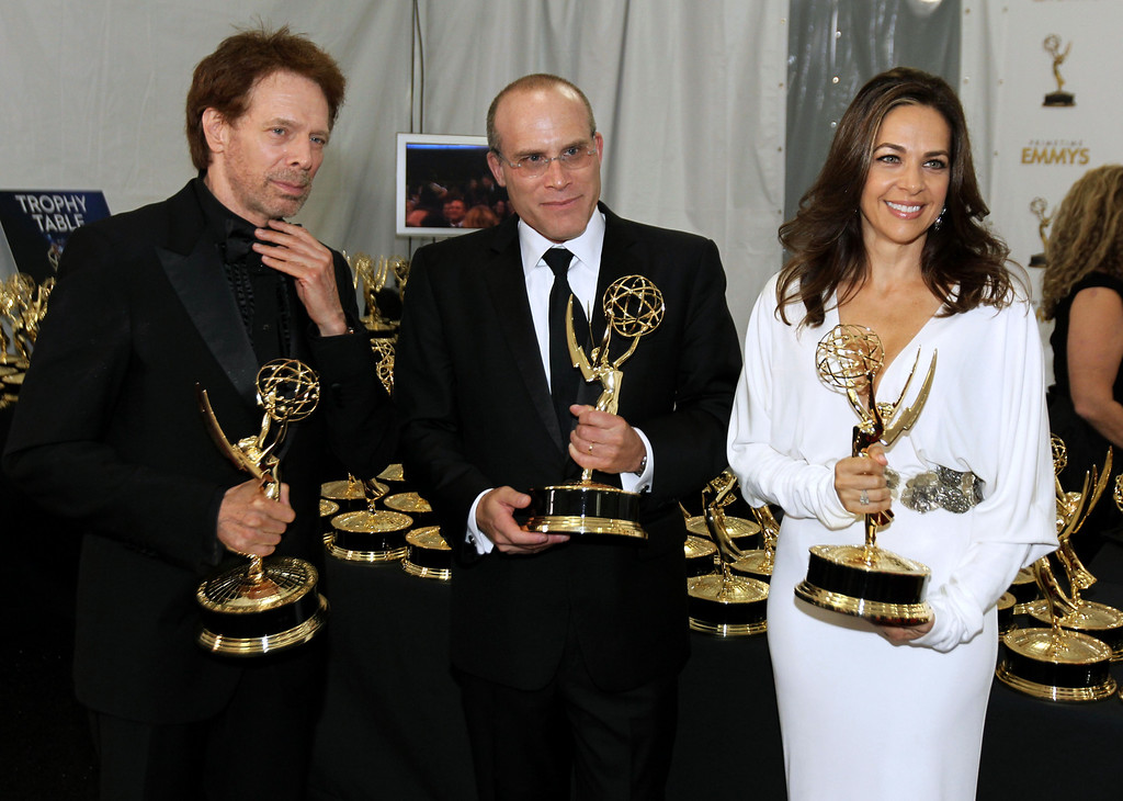 ". Producer Jerry Bruckheimer, from left, Jonathan Littman and Elise Doganieri, winners of the Outstanding Reality-Competition Program for ""The Amazing Race\"", poses backstage at the 64th Primetime Emmy Awards at the Nokia Theatre on Sunday, Sept. 23, 2012, in Los Angeles. (Photo by Matt Sayles/Invision/AP)"