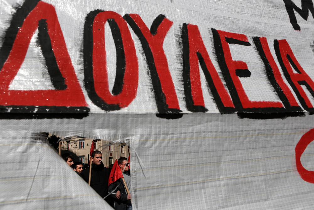 ". Protesters march during an anti-austerity rally in central Athens February 20, 2013. Tens of thousands of Greeks took to the streets of Athens on Wednesday during a nationwide strike against wage cuts and high taxes that kept ferries stuck in ports, schools shut and hospitals with only emergency staff. The banner reads, ""Jobs\""    REUTERS/John Kolesidis"