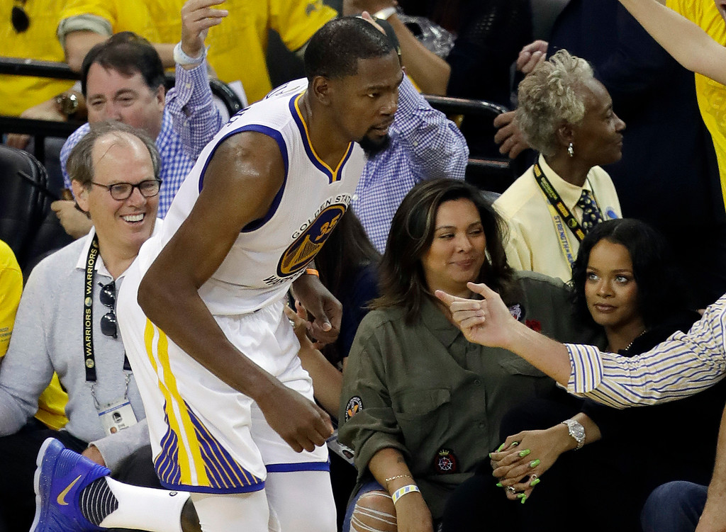 . Singer Rihanna, right, watches as Golden State Warriors\' Kevin Durant, left, runs past during the second half in Game 1 of basketball\'s NBA Finals against the Cleveland Cavaliers Thursday, June 1, 2017, in Oakland, Calif. (AP Photo/Marcio Jose Sanchez)