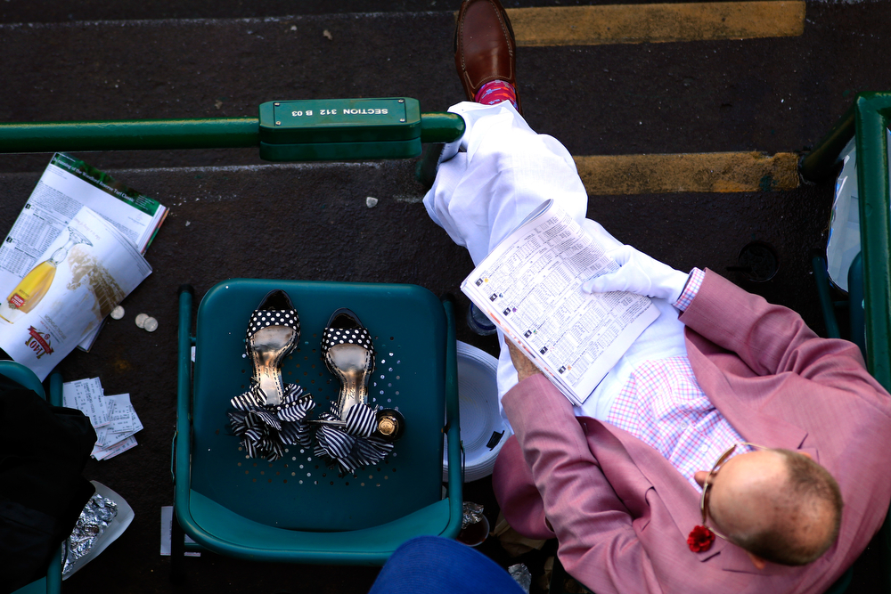 Description of . A spectator sits next to a pair of shoes prior to the 140th running of the Kentucky Derby at Churchill Downs on May 3, 2014 in Louisville, Kentucky.  (Photo by Jamie Squire/Getty Images)