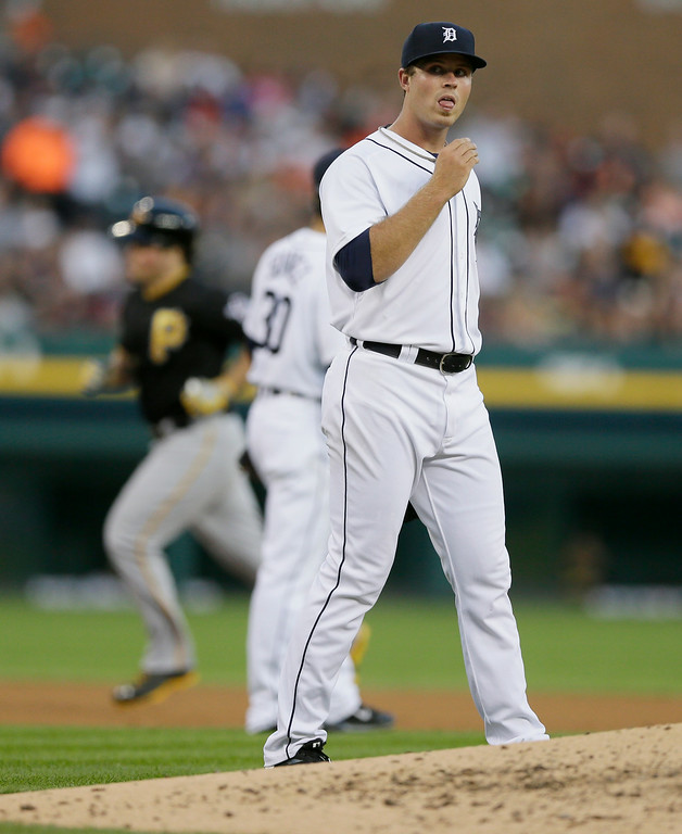 . Pittsburgh Pirates\' Travis Snider rounds the bases on his two-run home run as Detroit Tigers starting pitcher Buck Farmer walks on the mound during the fourth inning of an interleague baseball game, Wednesday, Aug. 13, 2014 in Detroit. (AP Photo/Carlos Osorio)