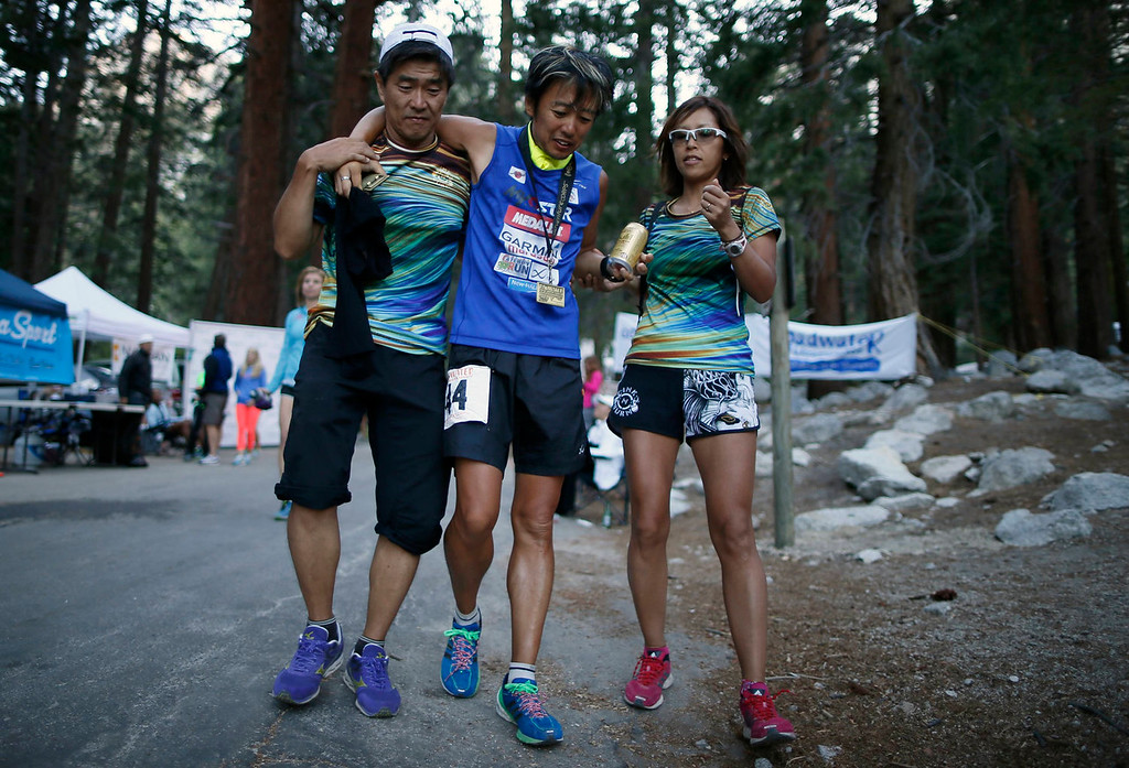 . Nobumi Iwamoto (C) of Japan, 47, hobbles away from the finish line after completing the Badwater Ultramarathon at the foot of Mount Whitney, California July 16, 2013. The 135-mile (217 km) race, which bills itself as the world\'s toughest foot race, goes from Death Valley to Mount Whitney, California in temperatures which can reach 130 degrees Fahrenheit (55 Celsius). Picture taken July 16, 2013.  REUTERS/Lucy Nicholson