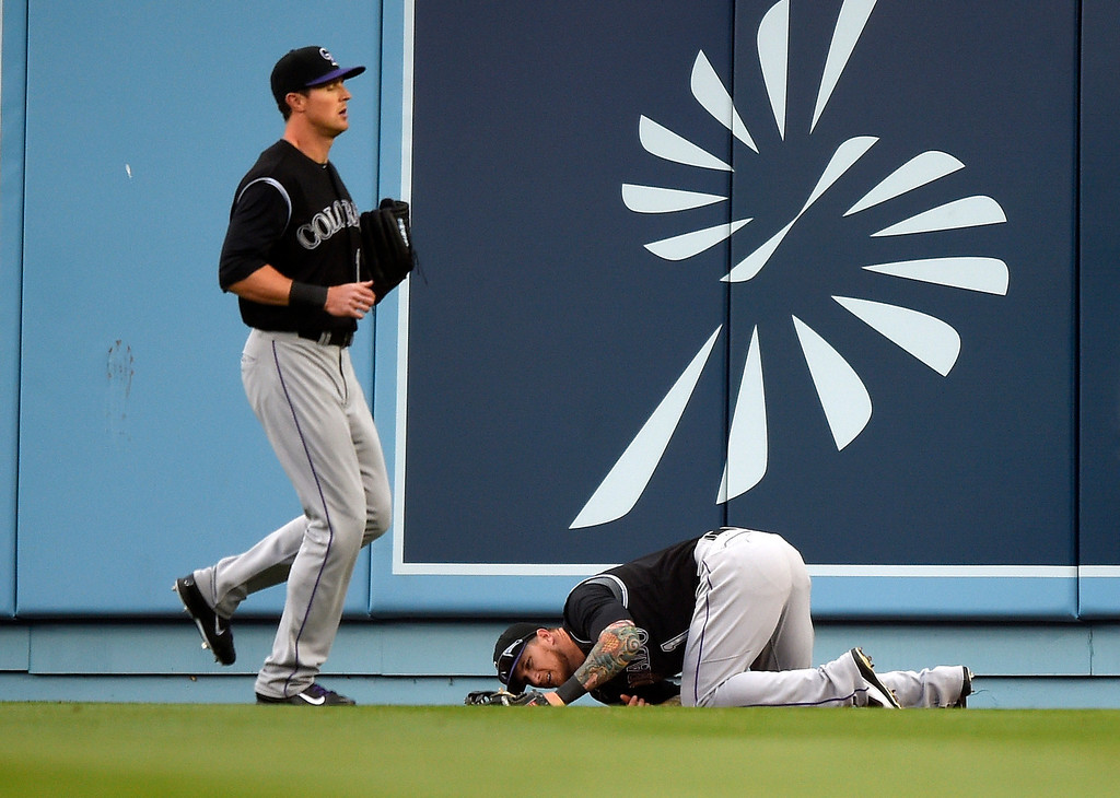 . Colorado Rockies center fielder Brandon Barnes, right, lies on the ground as left fielder Drew Stubbs approaches after Barnes wasn\'t able to catch a ball for a solo home run by Los Angeles Dodgers\' Matt Kemp during the third inning of a baseball game, Saturday, April 26, 2014, in Los Angeles. (AP Photo/Mark J. Terrill)