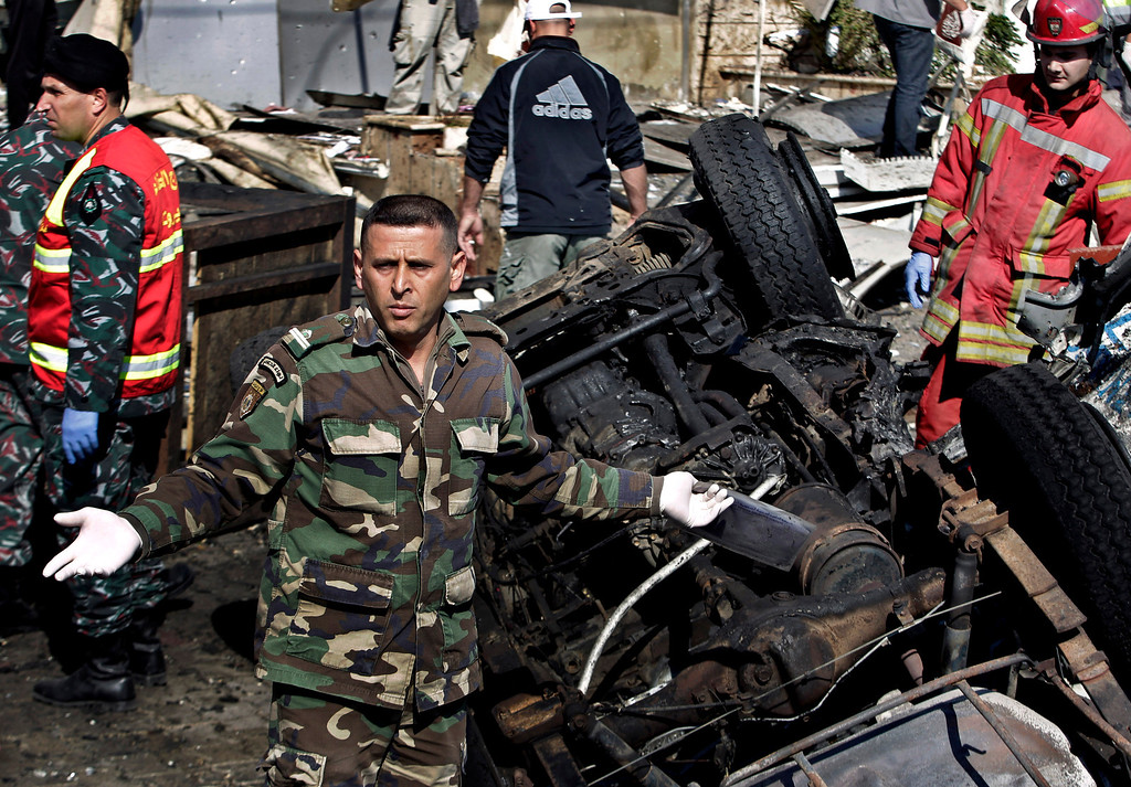 . Lebanese army investigators gather next to burned and damaged cars at the site of explosions, in the suburb of Beir Hassan, Beirut, Lebanon, Wednesday, Feb. 19, 2014. T (AP Photo/Bilal Hussein)