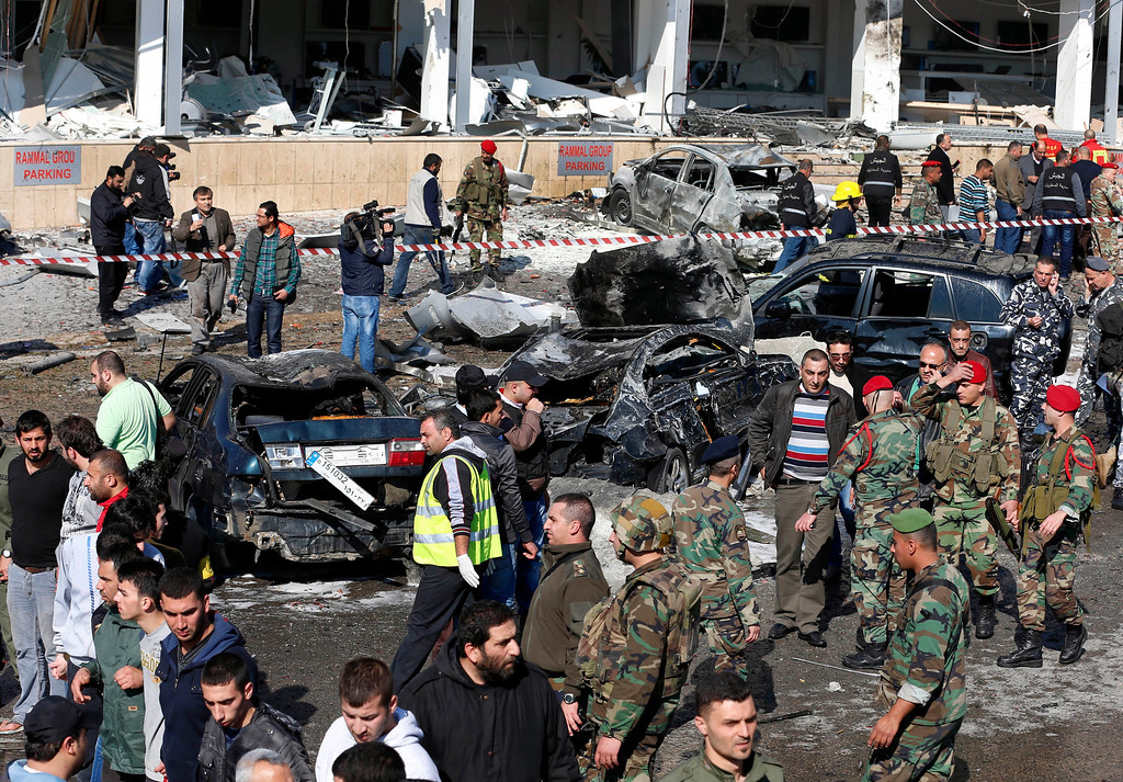 . Lebanese army investigators and citizens gather next to burned and damaged cars at the site of an explosion, near the Kuwaiti Embassy and Iran\'s cultural center, in the suburb of Beir Hassan, Beirut, Lebanon, Wednesday, Feb. 19, 2014. (AP Photo/Hassan Ammar)