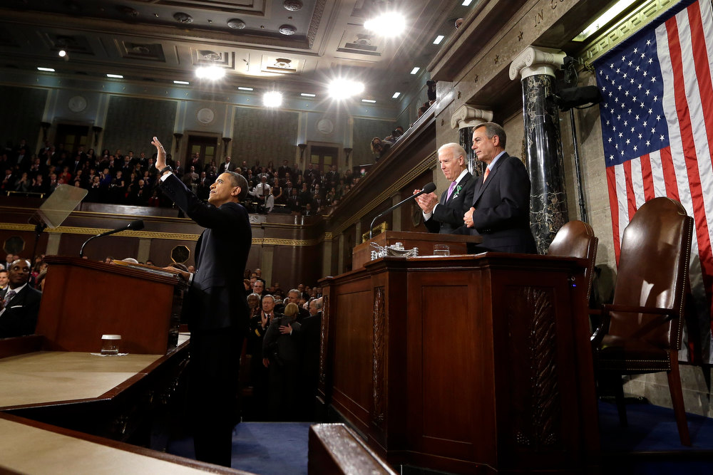 Description of . President Barack Obama waves before giving his State of the Union address during a joint session of Congress on Capitol Hill in Washington, Tuesday Feb. 12, 2013. Vice President Joe Biden and House Speaker John Boehner of Ohio stand behind the president. (AP Photo/Charles Dharapak, Pool)