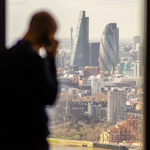Silhouette of man on phone in front of London financial district