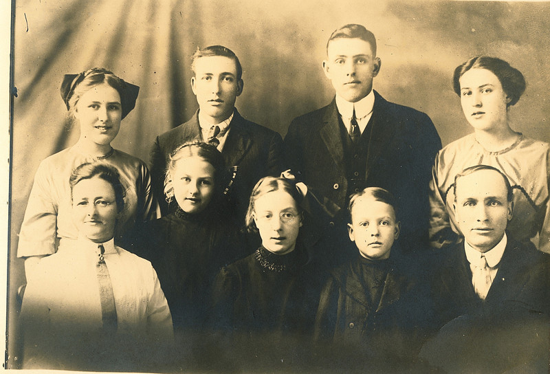 "Front row: Fannie Belle (Hays) Dew (1871-1919), Alice Martha Dew (1902-1999), Glenna Ellen Dew (1900-1997), Burl Orville Dew (1904-2001), William Alfred Dew (1869-1965) Back row: Josie Louisa Dew (1897-1999), Byron Elmer Dew (1893-1986), Perry Winfield Dew (1891-1975), Mary Lavinna Dew (1895-1992), Written in the Rogers Reunion Photo Album Volume III page 16 under the photo ""Dew Family   Josie, Elmer, Perry, Mary, Fannie (mother), Alice, Glenna, Burl, William (father)"""