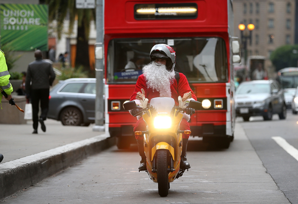 Description of . A man dressed as Santa Claus rides a motorcycle in Union Square on December 14, 2012 in San Francisco, California.  With less than two weeks before Christmas, San Franciscans are getting into the holiday spirit.  (Photo by Justin Sullivan/Getty Images)