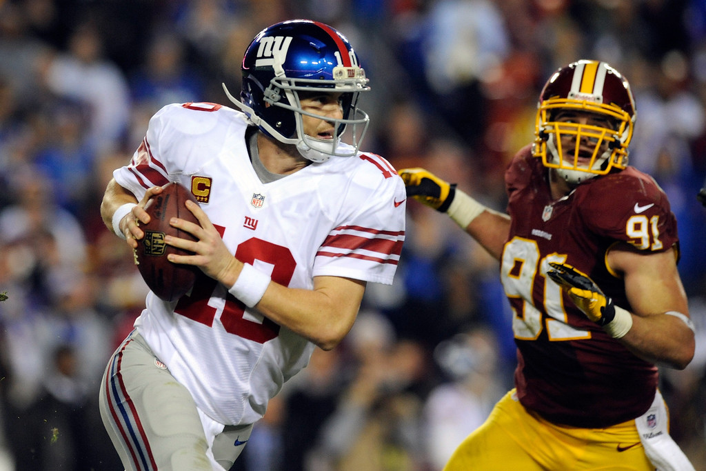 . LANDOVER, MD - DECEMBER 03:  Quarterback Eli Manning #10 of the New York Giants scrambles as he is being chased by Ryan Kerrigan #91 of the Washington Redskins in the third quarter against the Washington Redskins at FedExField on December 3, 2012 in Landover, Maryland.  (Photo by Patrick McDermott/Getty Images)