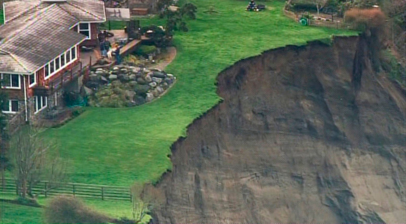 . Homes are seen at the edge of a cliff following a landslide on Whidbey Island, Washington in this frame grab taken from video courtesy of KING 5 News, March 27, 2013. The landslide, which occurred early morning March 27, heavily damaged one home and is threatening over 30 others in the community of Ledgewood. REUTERS/KING 5 News/Handout