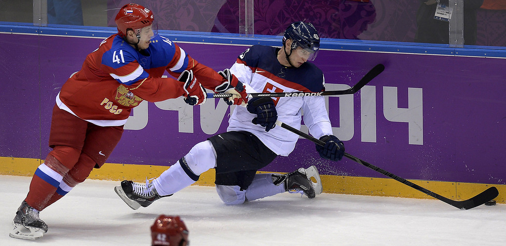 . Slovakia\'s Tomas Surovy (R) challenges Russia\'s Nikolai Kulyomin during the Men\'s Ice Hockey Group A match between Russia and Slovakia at the Bolshoy Ice Dome in Sochi during the Sochi Winter Olympics on February 16, 2014.   ALEXANDER NEMENOV/AFP/Getty Images