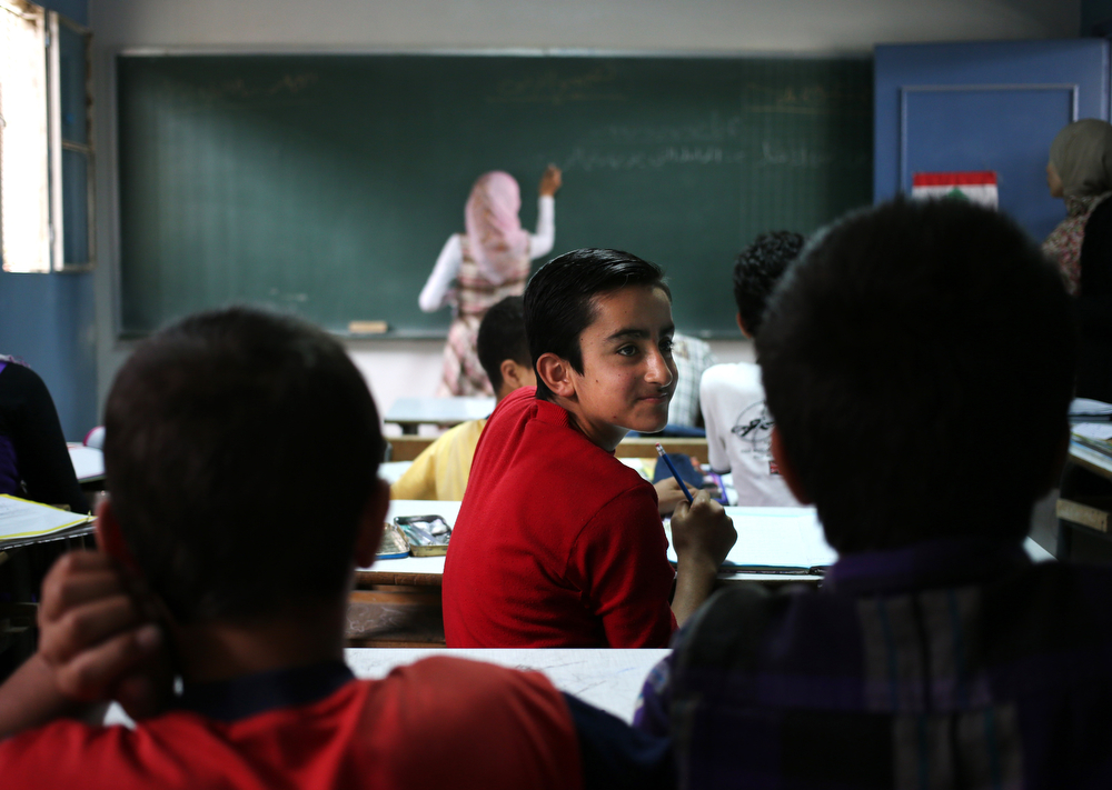 . In this picture taken on Thursday, May 29, 2014, a Syrian refugee student, center, attends with other schoolmates an Arabic lesson at a Lebanese public school where only Syrian students attend classes in the afternoon, in Kaitaa village in north Lebanon. (AP Photo/Hussein Malla)