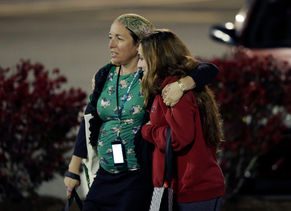 . Two women walk in the parking lot of the Garden State Plaza Mall with officials standing guard following reports of a shooter, Monday, Nov. 4, 2013, in Paramus, N.J. Hundreds of law enforcement officers converged on the mall Monday night after witnesses said multiple shots were fired there. (AP Photo/Julio Cortez)