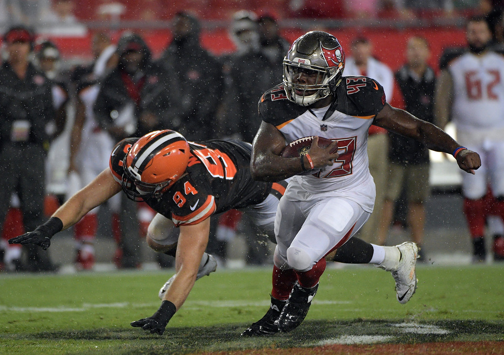 . Tampa Bay Buccaneers running back Peyton Barber (43) eludes Cleveland Browns defensive end Carl Nassib (94) during the fourth quarter of an NFL preseason football game Saturday, Aug. 26, 2017, in Tampa, Fla. (AP Photo/Phelan Ebenhack)