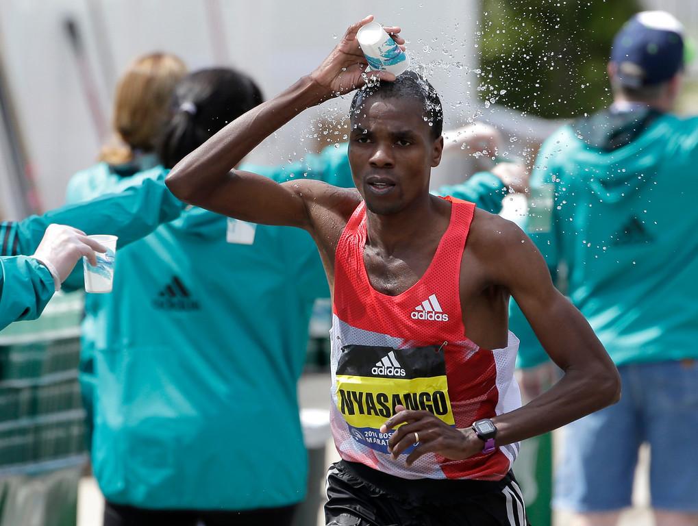 . Cutbert Nyasango, of Zimbabwe, douses himself with water as he runs through Wellesley, Mass., during the 120th Boston Marathon on Monday, April 18, 2016. (AP Photo/Steven Senne)