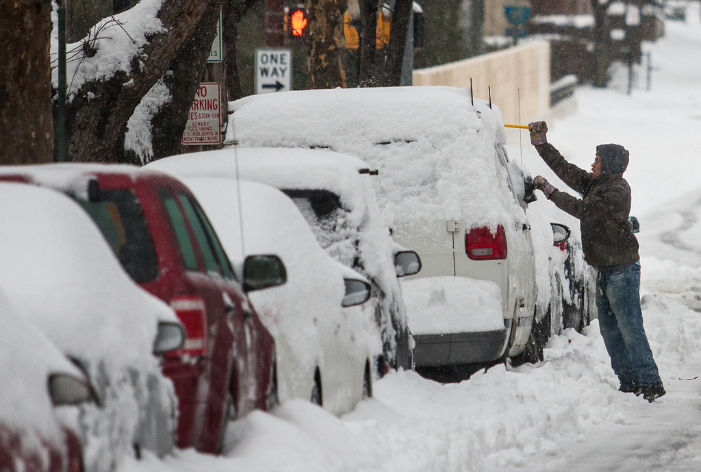 . A man clears off his car on 10th street, in downtown Wilmington, Del. on Thursday morning, Feb. 13, 2014. The city saw nearly a foot of snow fall over night, and residents were forced to dig out in blowing sleet in the morning. (AP Photo/The News Journal, Kyle Grantham)