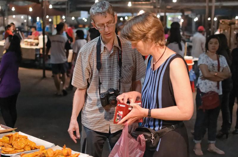 Ulmar kennt sich auf dem Markt gut aus und berät Helga beim Einkauf der überbackenen Auberginen und Bananen.