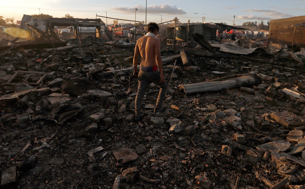 . A man walks  through the scorched ground of the open-air San Pablito fireworks market, in Tultepec, outskirts of Mexico City, Mexico, Tuesday, Dec. 20, 2016.  An explosion ripped through Mexico�s best-known fireworks market where most of the fireworks stalls were completely leveled. According to the Mexico state prosecutor there are dozens dead. (AP Photo/Eduardo Verdugo)