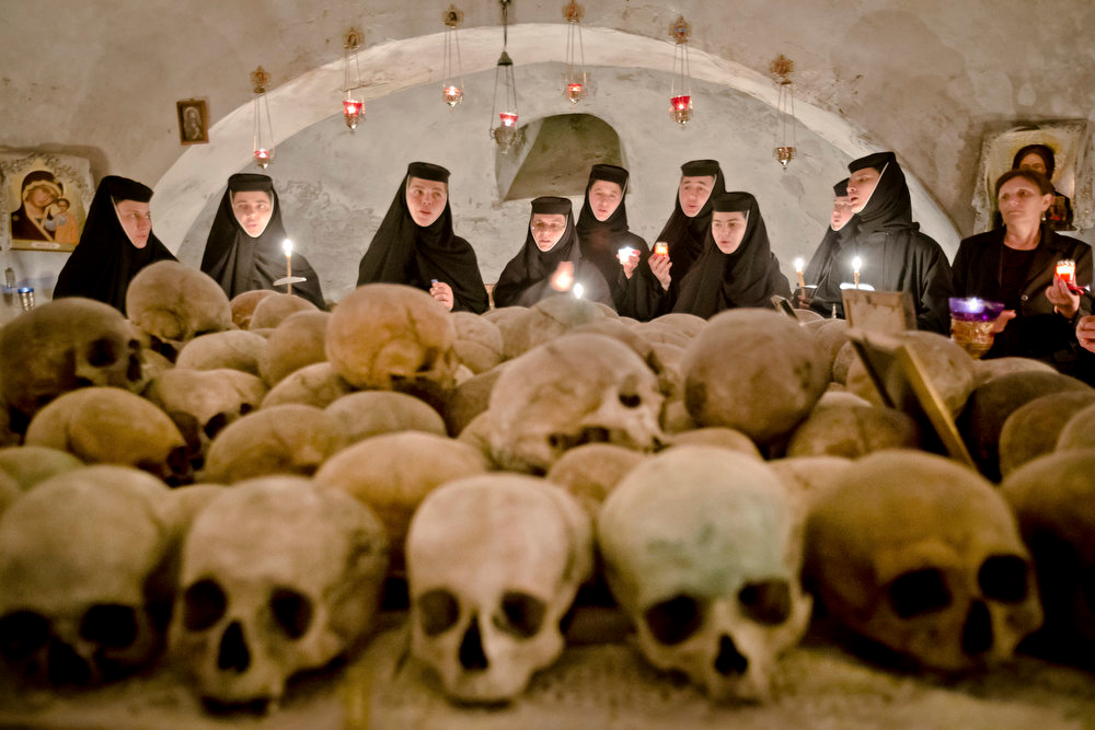 . Romanian orthodox nuns sing in the ossuary at the Pasarea monastery, outside Bucharest, Romania, Sunday, May 5, 2013, during the Easter Religious service. The ossuary, containing mostly remains of the nuns that lived at the monastery is briefly opened on Easter night. (AP Photo/Vadim Ghirda)