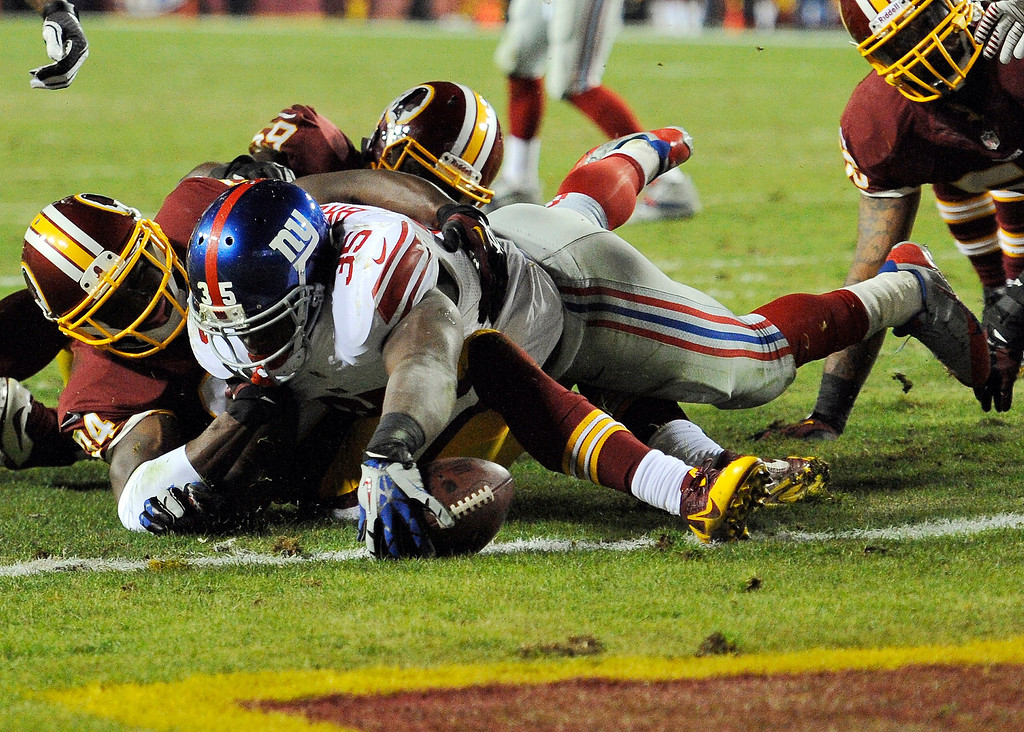 . New York Giants running back Andre Brown (35) stretches for a touchdown over Washington Redskins defensive back Trenton Robinson, left, during the second half of an NFL football game Sunday, Dec. 1, 2013, in Landover, Md. (AP Photo/Nick Wass)