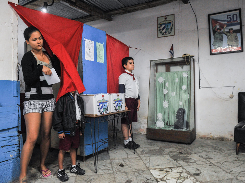 Description of . A Cuban leaves the booth after casting her vote at a polling station in Havana on February 3, 2013. Cubans on Sunday elected provincial delegates to to the People's Power assemblies and parliamentary deputies. AFP PHOTO / STR/AFP/Getty Images