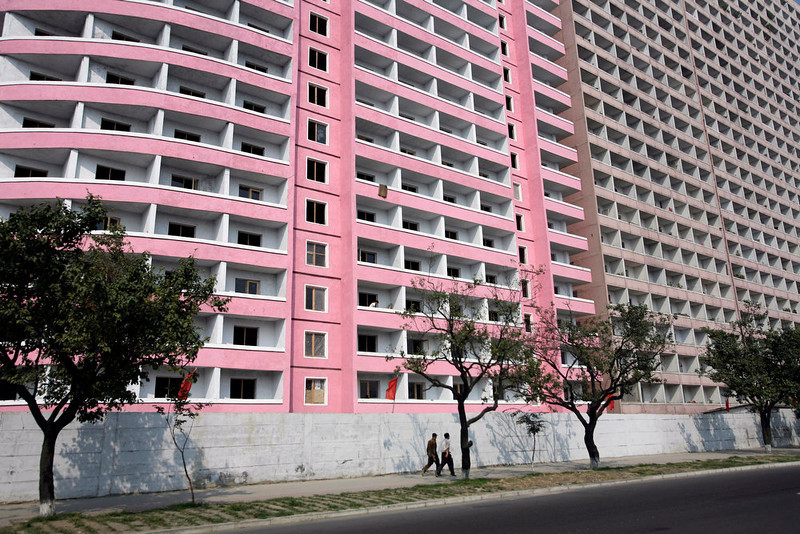 . North Koreans pass by a newly finished apartment block in Pyongyang, North Korea on Friday, Sept. 19, 2008. North Korea has nearly completed its project to give a facelift to its capital. The communist nation launched the makeover project to mark the 60th anniversary of its foundation.  (AP Photo/David Guttenfelder)