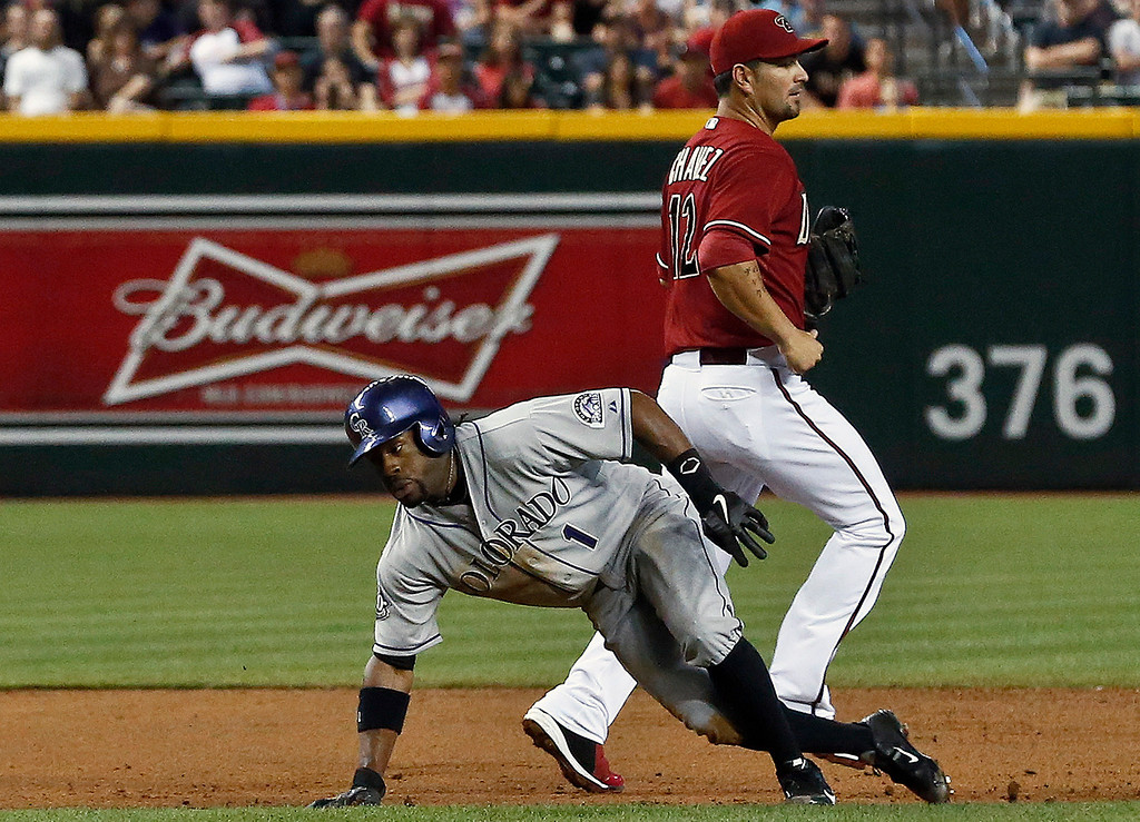 . Colorado Rockies\' Eric Young Jr. (1) slips past Arizona Diamondbacks\' Eric Chavez as he is caught in a rundown and eventually is tagged out during the third inning of a baseball game on Sunday, April 28, 2013, in Phoenix. (AP Photo/Ross D. Franklin)